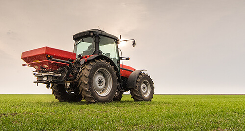Farm Insurance: Large, red tractor with a sprayer parked in a field