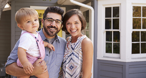 Home Insurannce: Young couple with a toddler standing in-front of their new home